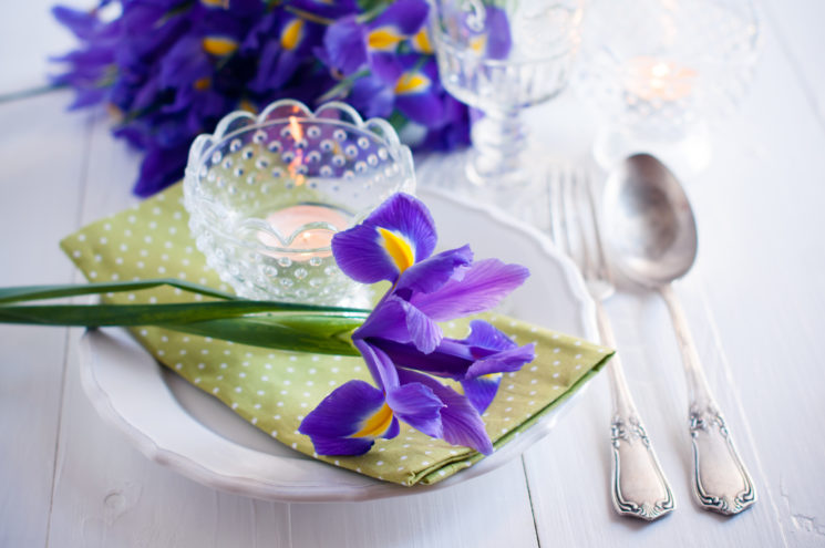 Festive table setting with purple iris flowers, vintage cutlery and candles.