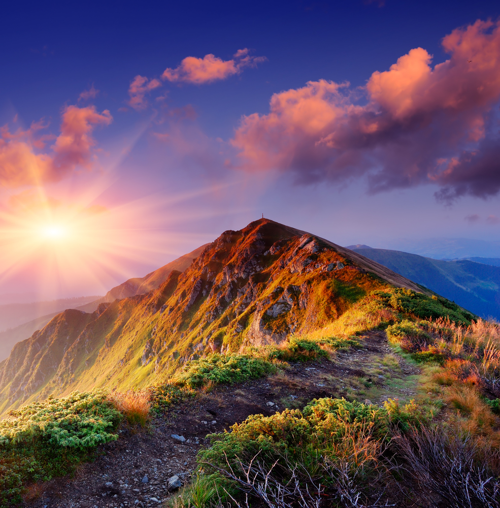 Beautiful summer sunrise in mountains. Path along the ridge leading to summit